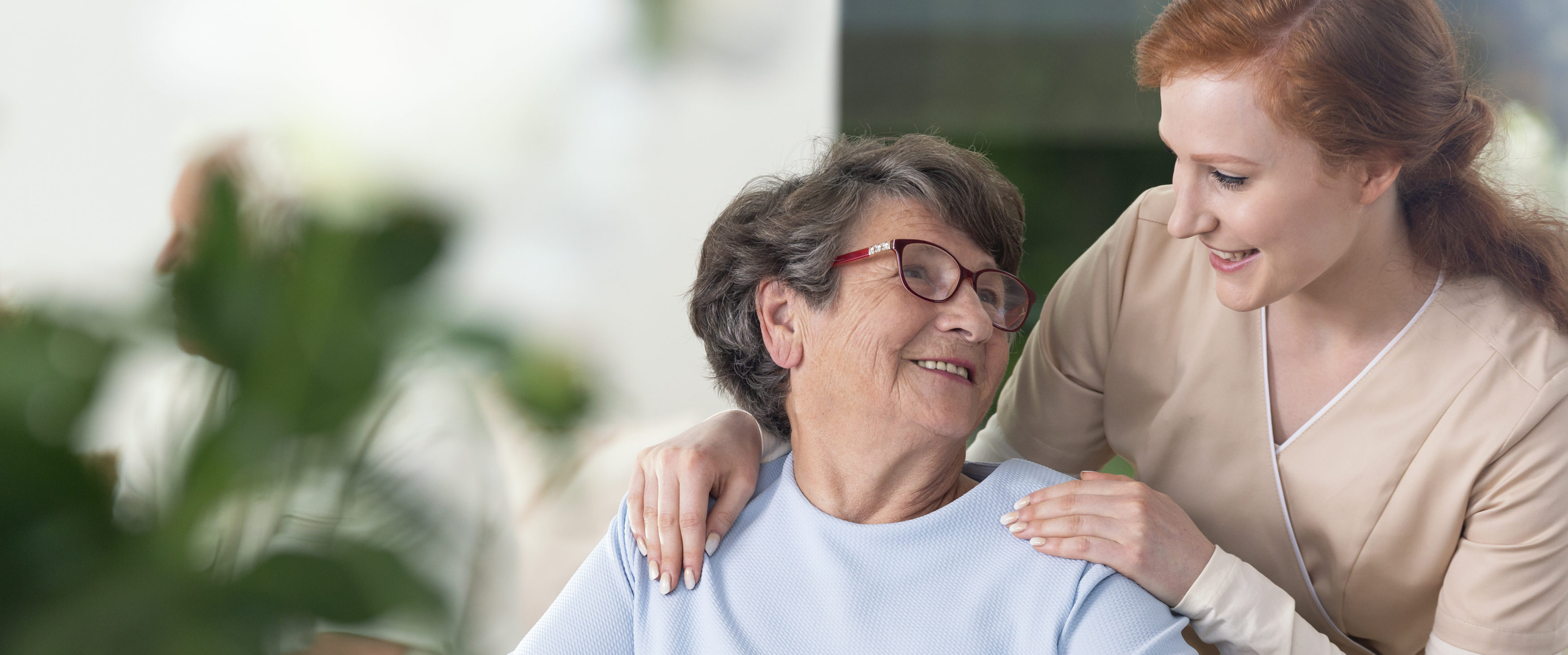 Close-up of a tender caregiver with her hands on the shoulders of a senior woman inside her home.